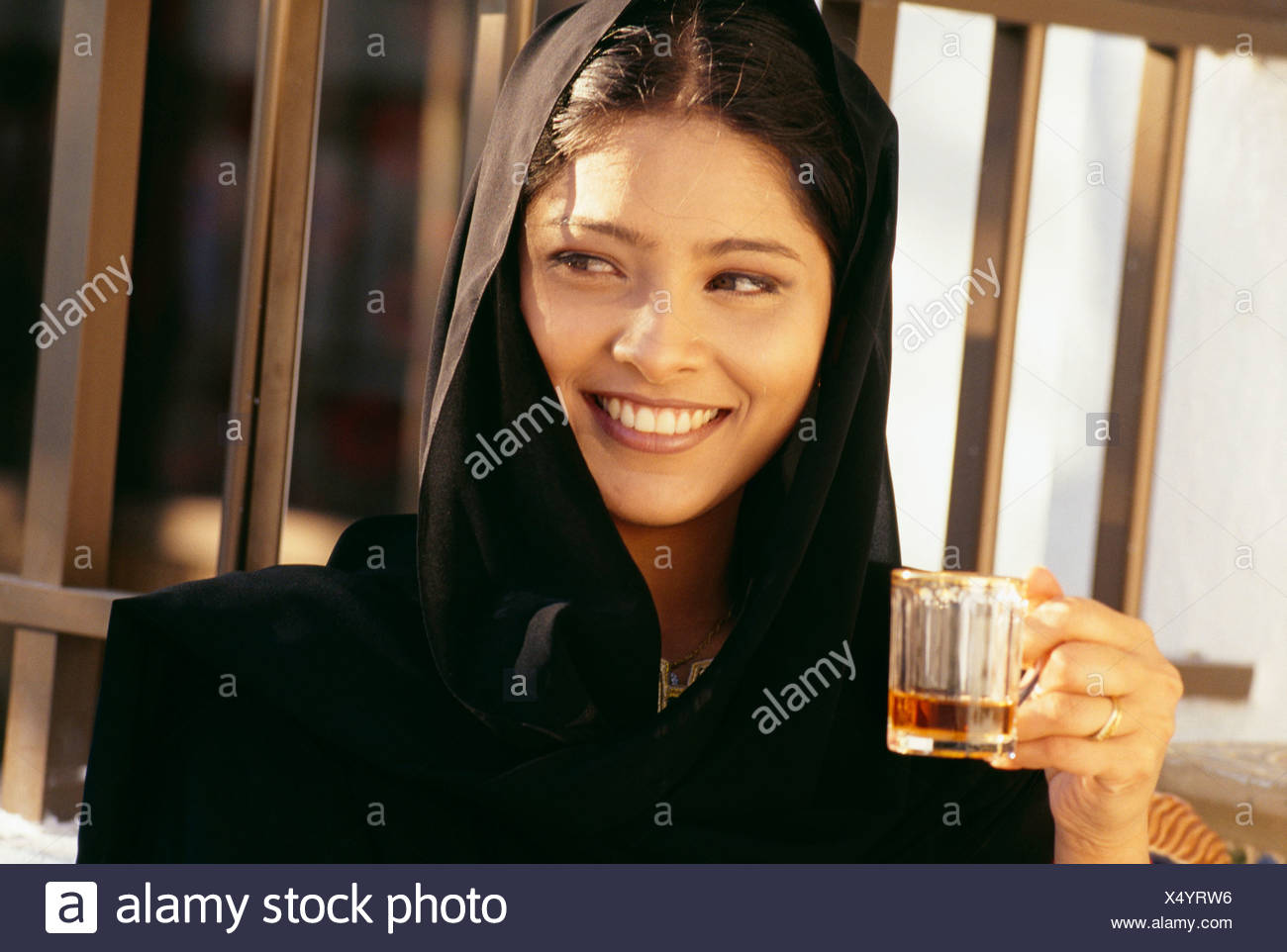 A young woman in burka smiles as she holds the glass. - Stock Image