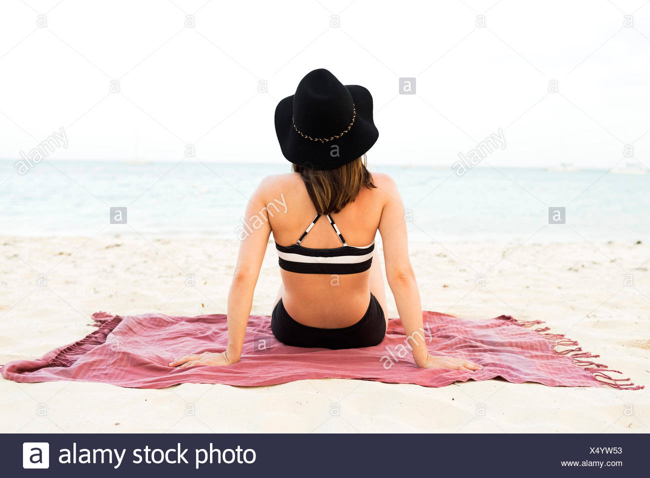 Woman in bikini relaxing on beach - Stock Image