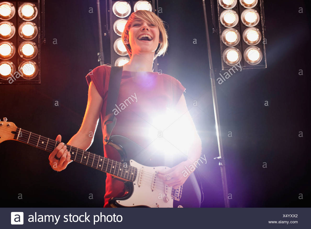 A woman playing electric guitar performing on stage - Stock Image