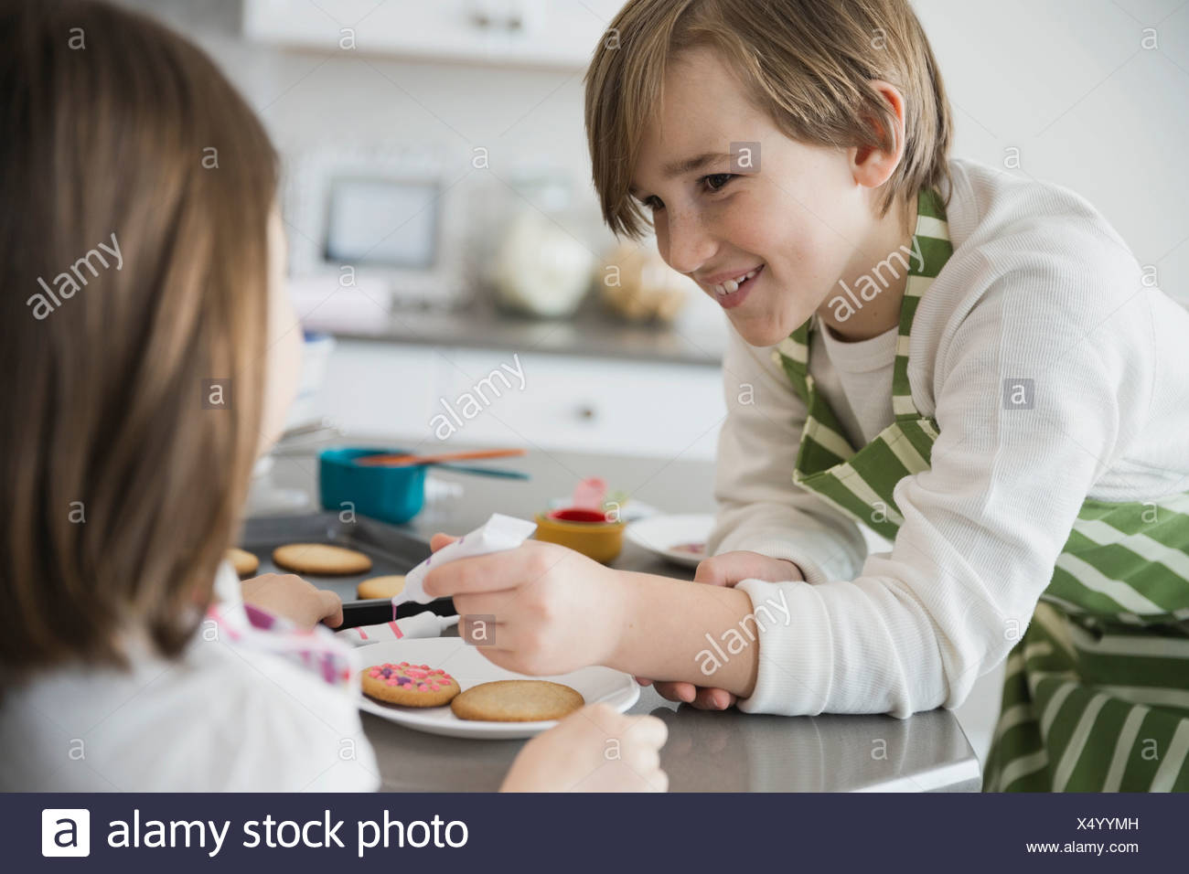 Siblings decorating cookies in kitchen - Stock Image