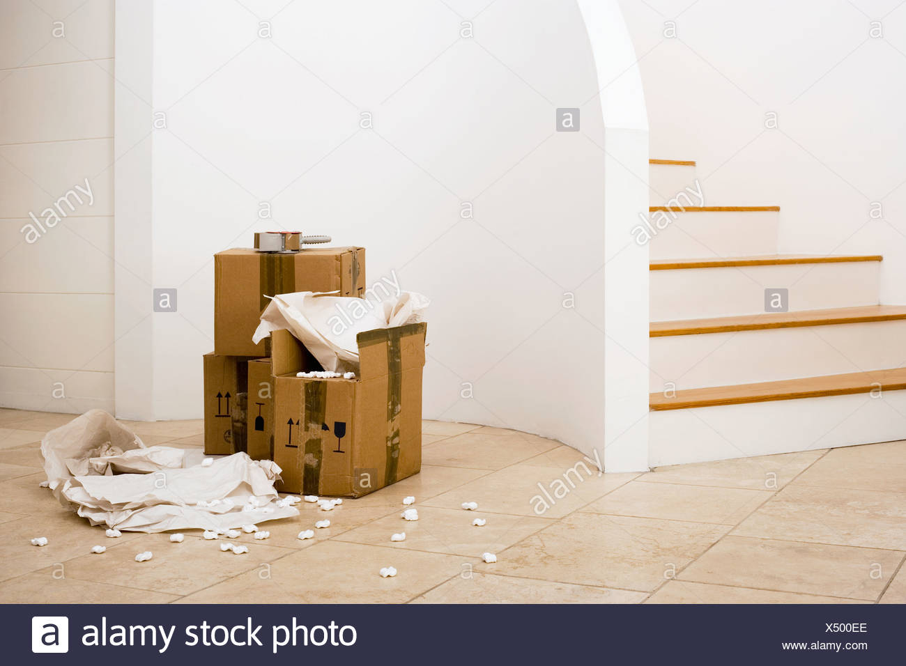 Small stack of boxes paper and packing foam beside staircase