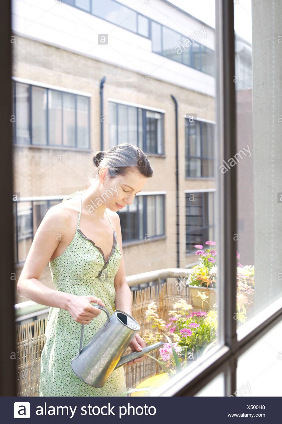 Woman on balcony watering flowers - Stock Image