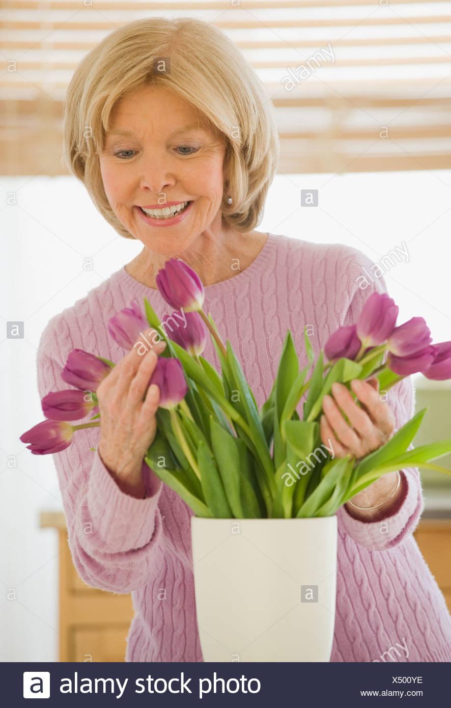 Senior woman arranging flowers Stock Photo