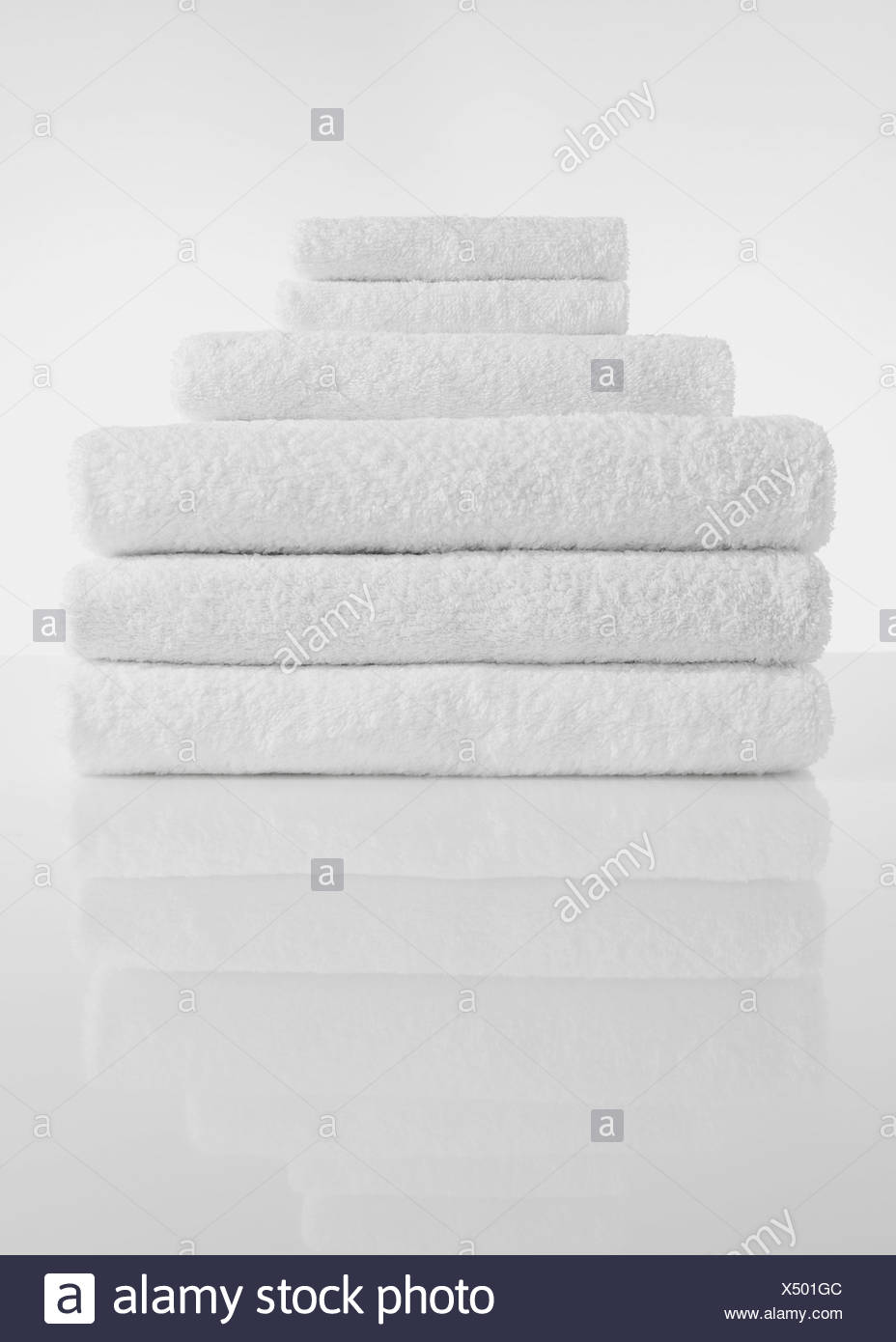 Stack of white towels on white background - Stock Image