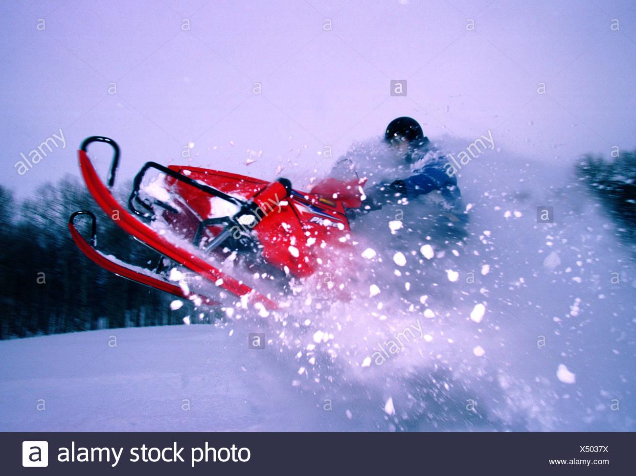 Snowmobile launching through powder snow - Stock Image