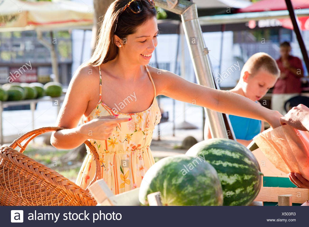 Young woman buying vegetables at market stall - Stock Image