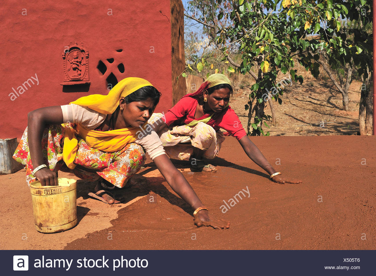 Two women plastering the floor of a courtyard with a mixture of cow dung and sand, Thar Desert, Rajasthan, India, Asia Stock Photo