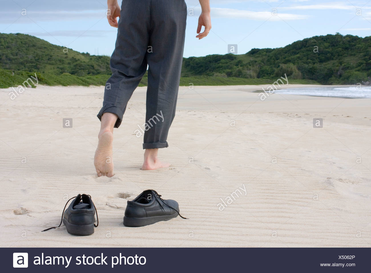 259ebc567 Businessman walking barefoot on a empty beach. Focus on his shoes in the  foreground
