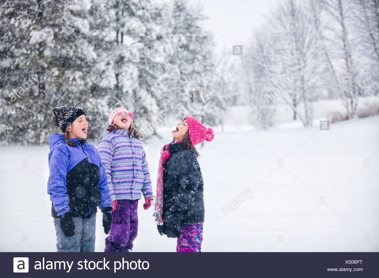 Friends catching snowflake on their tongues - Stock Image