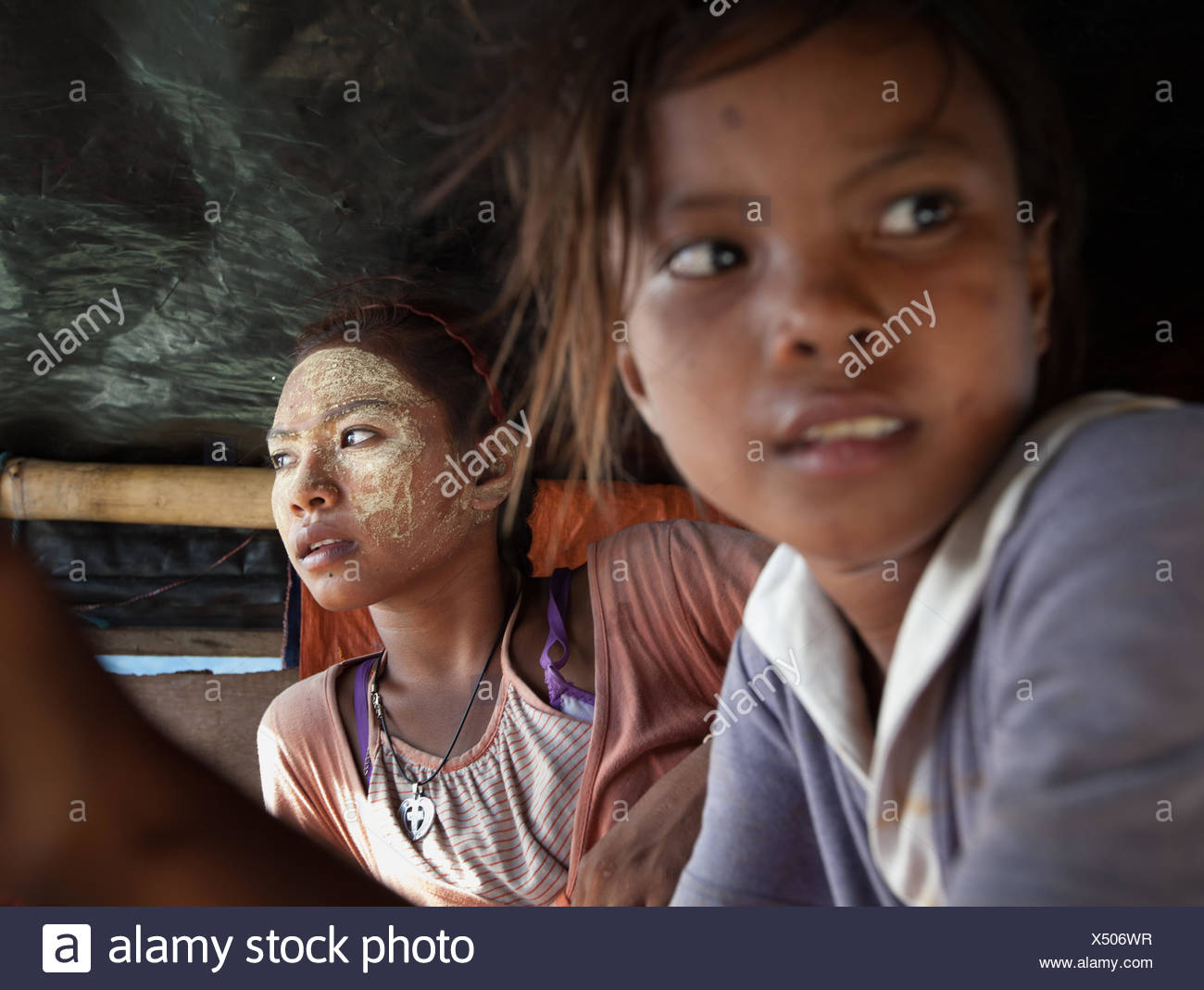 Her face dusted in bedak sejuk, a cooling powder made of rice and pandan leaves, a Bajau girl and her friend sit in a stilt house. - Stock Image