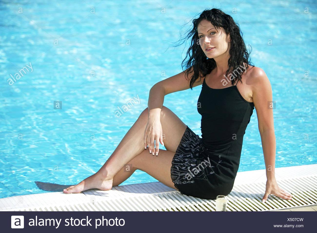 Frau Schwarzhaarig Pool Beckenrand Sitzen Jung Kleid Sommerkleid Barfuss Entspannt Gluecklich Freude Swimmingpool Schwimmbecken - Stock Image