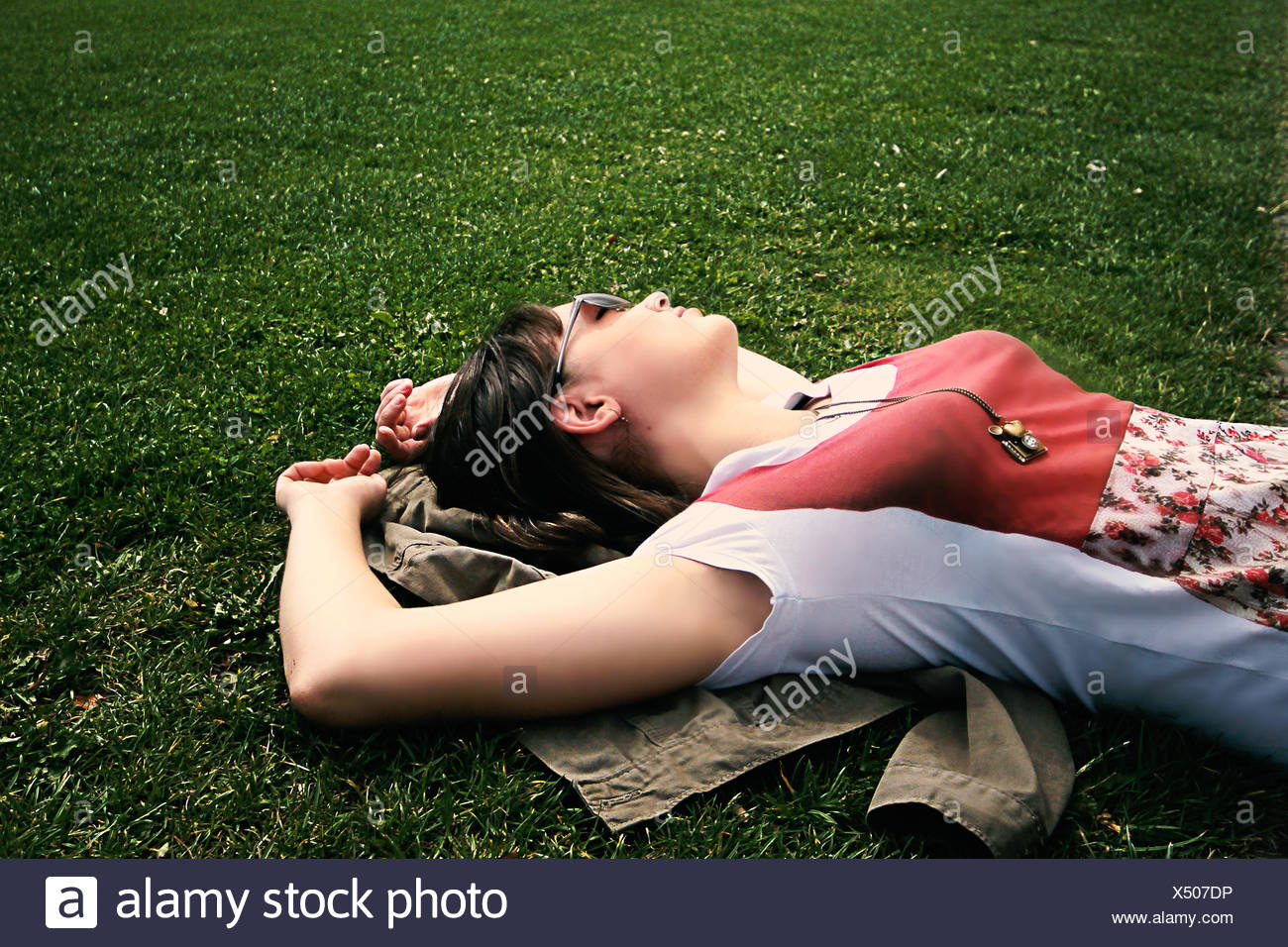 woman lying on grass relaxing - Stock Image
