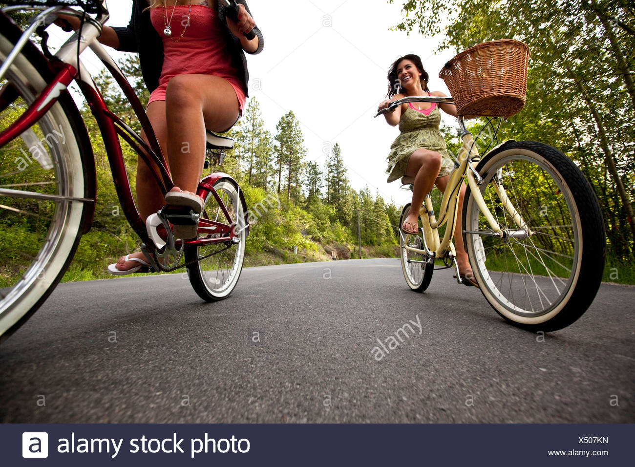 Women ride beach cruisers next to the lake in Idaho. - Stock Image