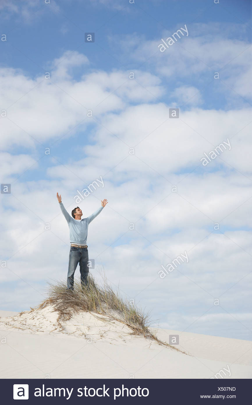 A man with his arms open atop a hill - Stock Image