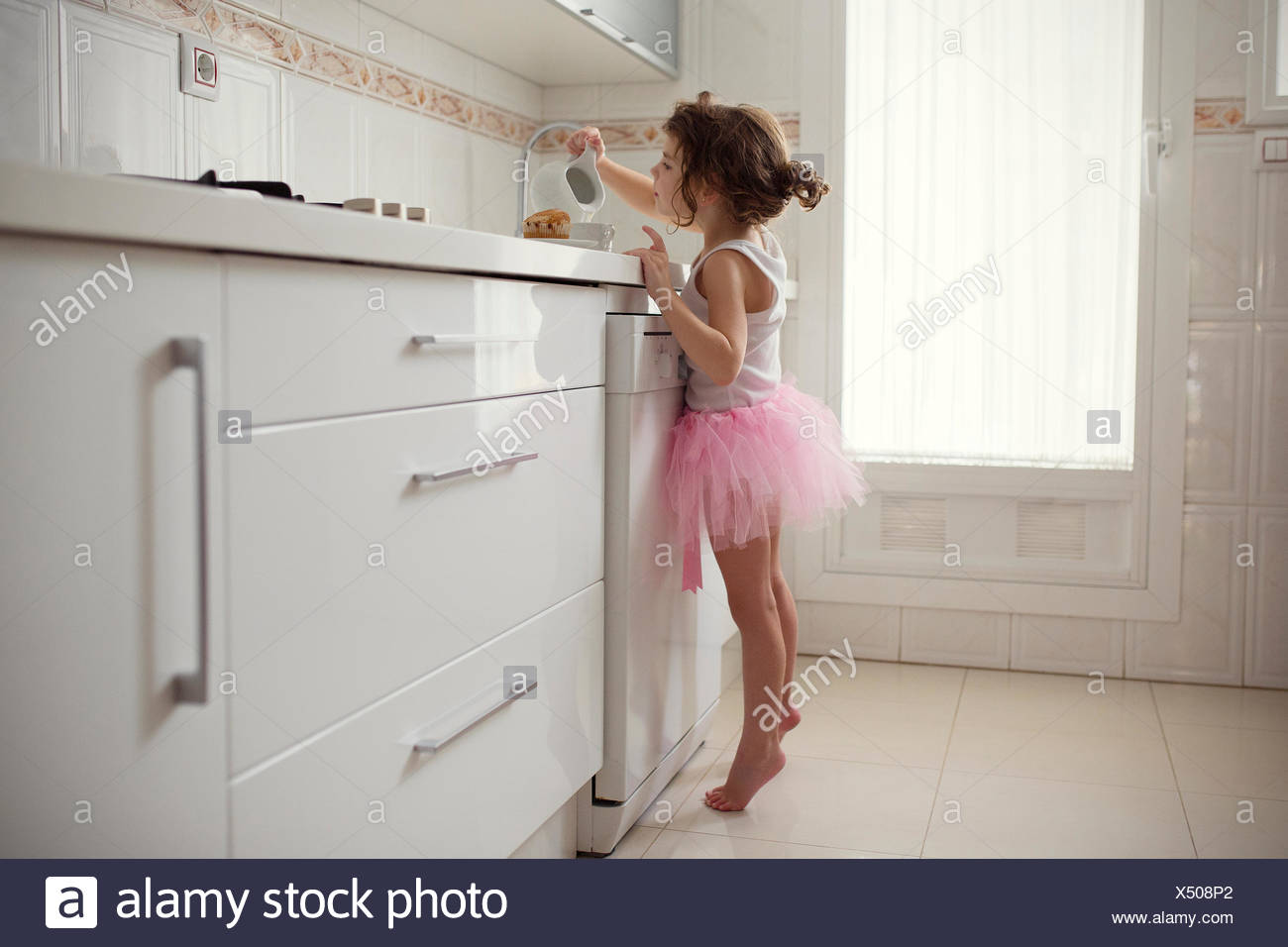 Girl in tutu standing in kitchen pouring milk into a cup - Stock Image