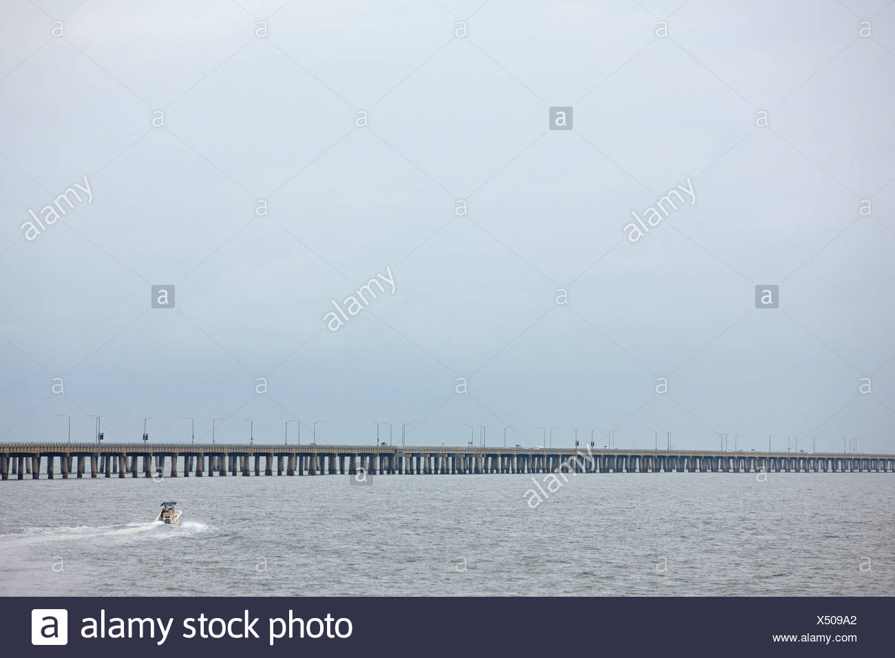 Small Boat Plies the Waters Near the Bridge Portion of the Chesapeake Bay Bridge Tunnel - Stock Image