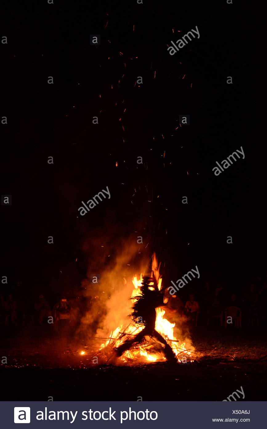 A costumed person in silhouette in front of a fire during a Baining fire dance. - Stock Image