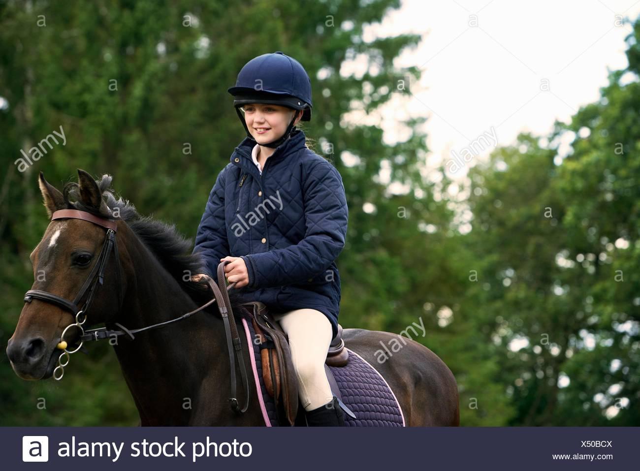 Girl horseback riding in countryside - Stock Image