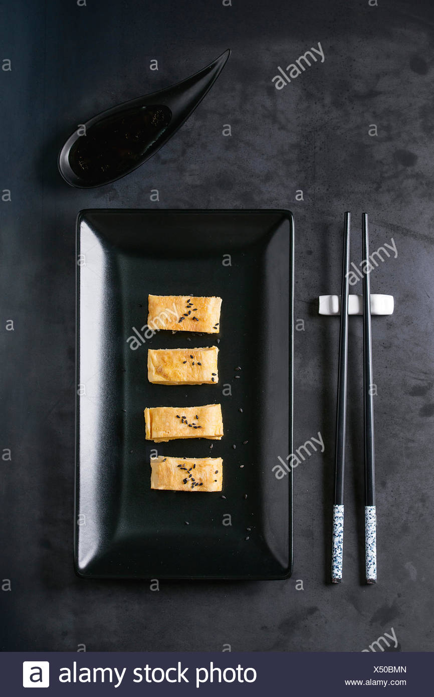 Japanese Rolled Omelet Tamagoyaki sliced with black seasame seeds and soy sauce, served in black square ceramic plate with chopsticks over dark metal  - Stock Image
