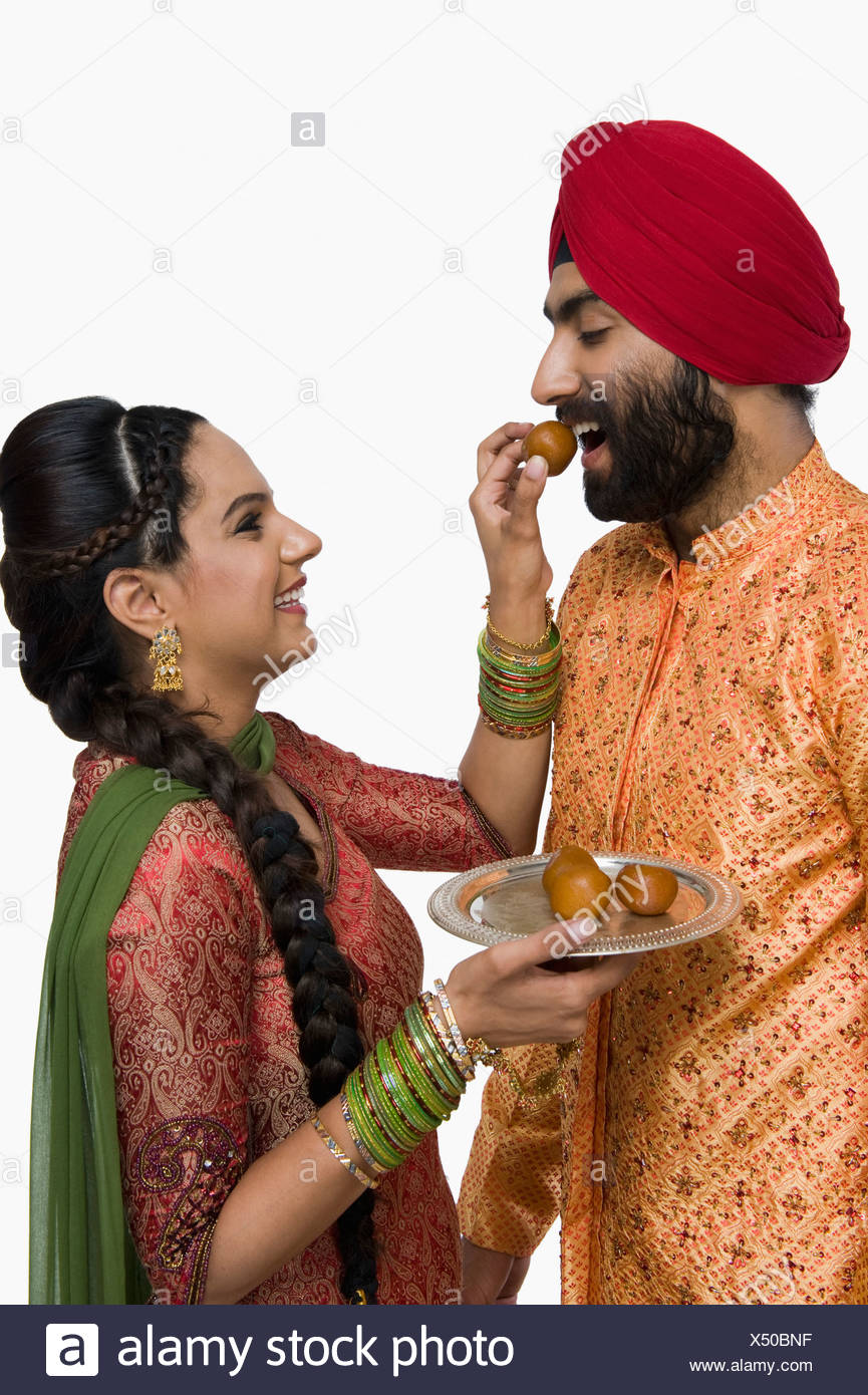 Woman feeding gulab jamun to her husband - Stock Image