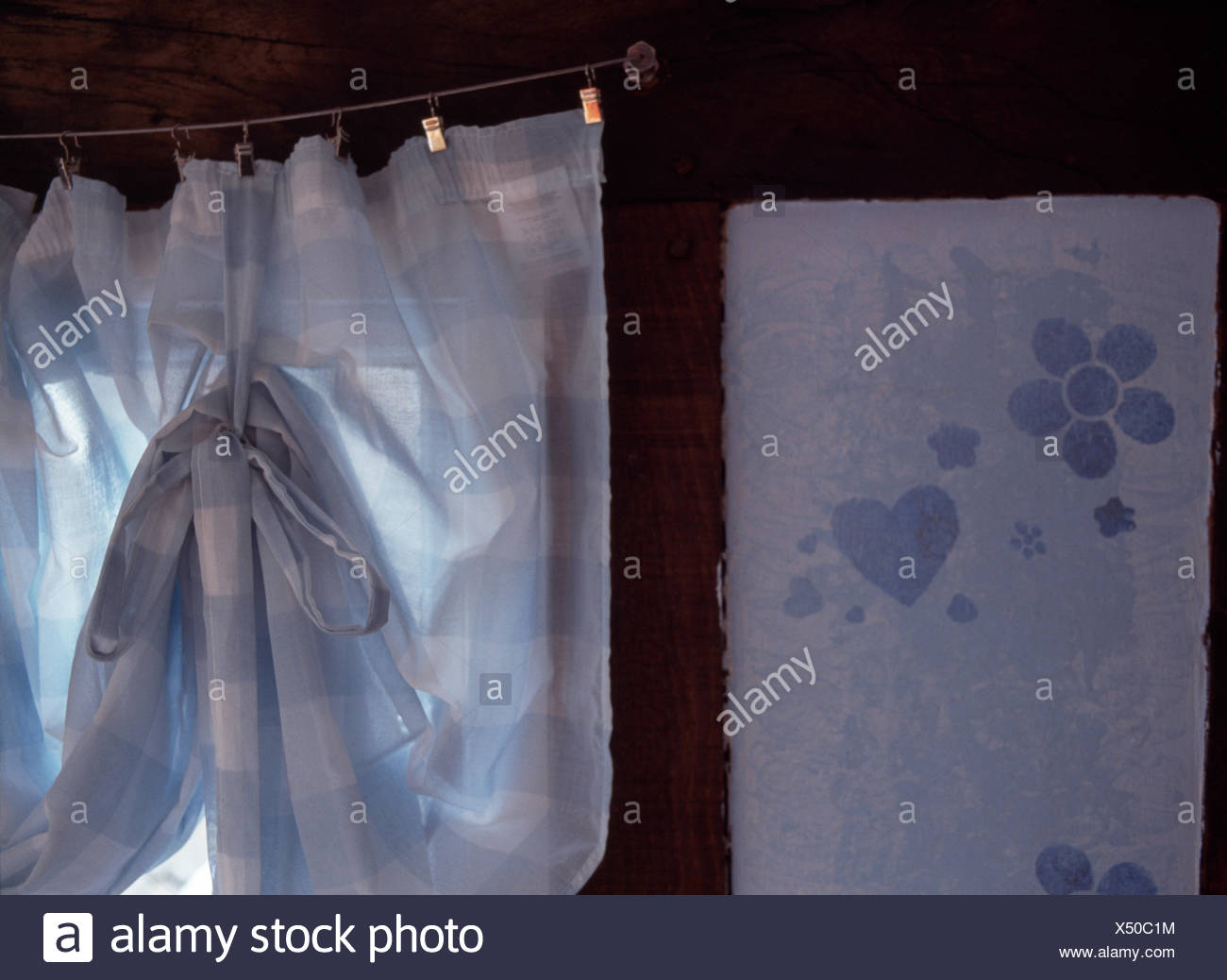 Close-up of a pale blue checked curtain on wire with metal clips beside a stenciled panel - Stock Image