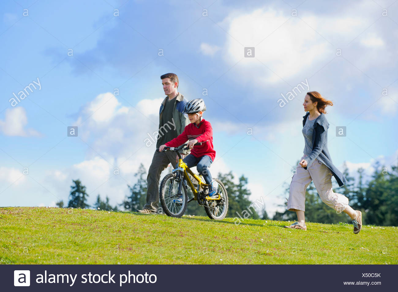 Parents keeping up with son riding bicycle - Stock Image