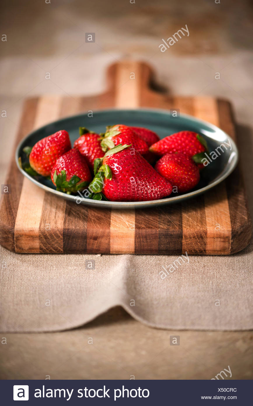 Blue plate of fresh strawberries on a rustic cutting board. - Stock Image