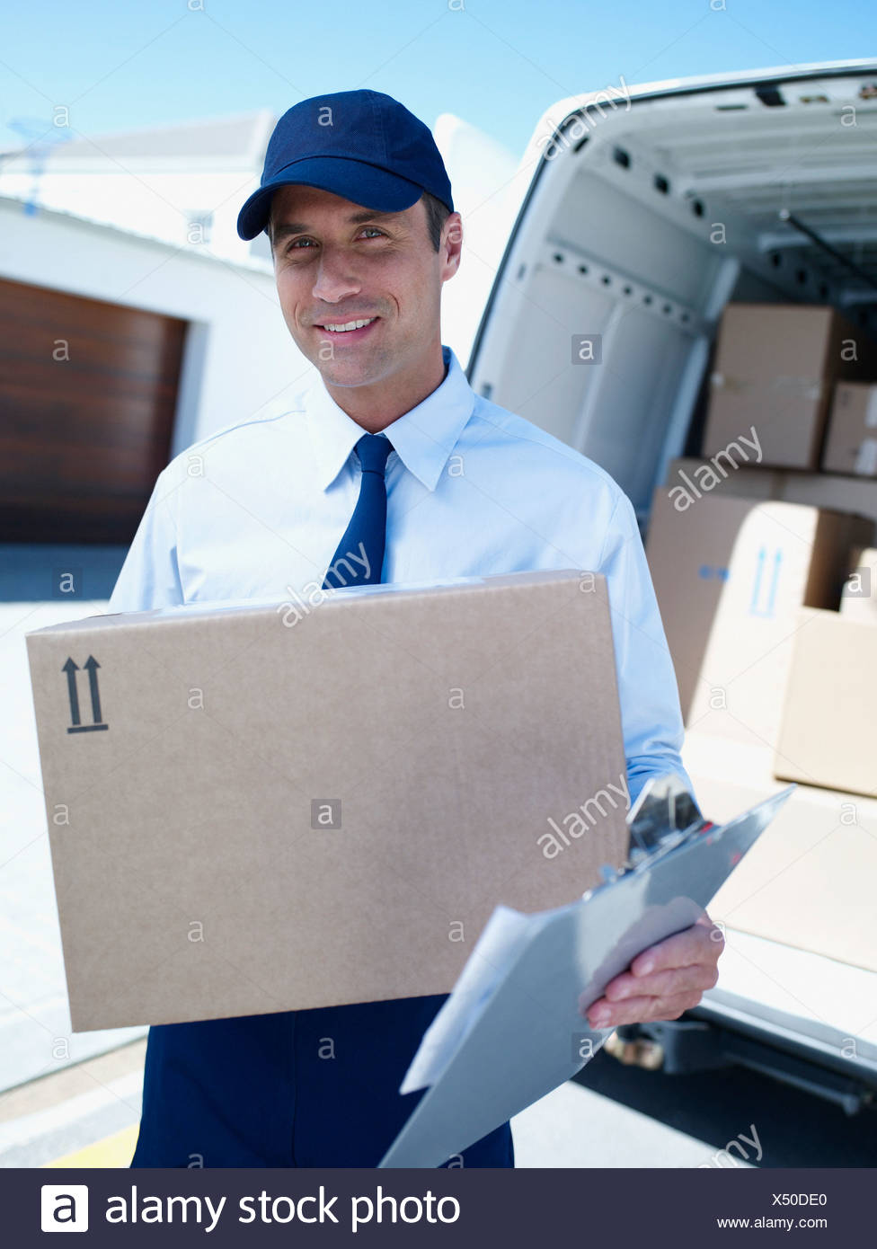 Male delivery person in cap with van and boxes - Stock Image