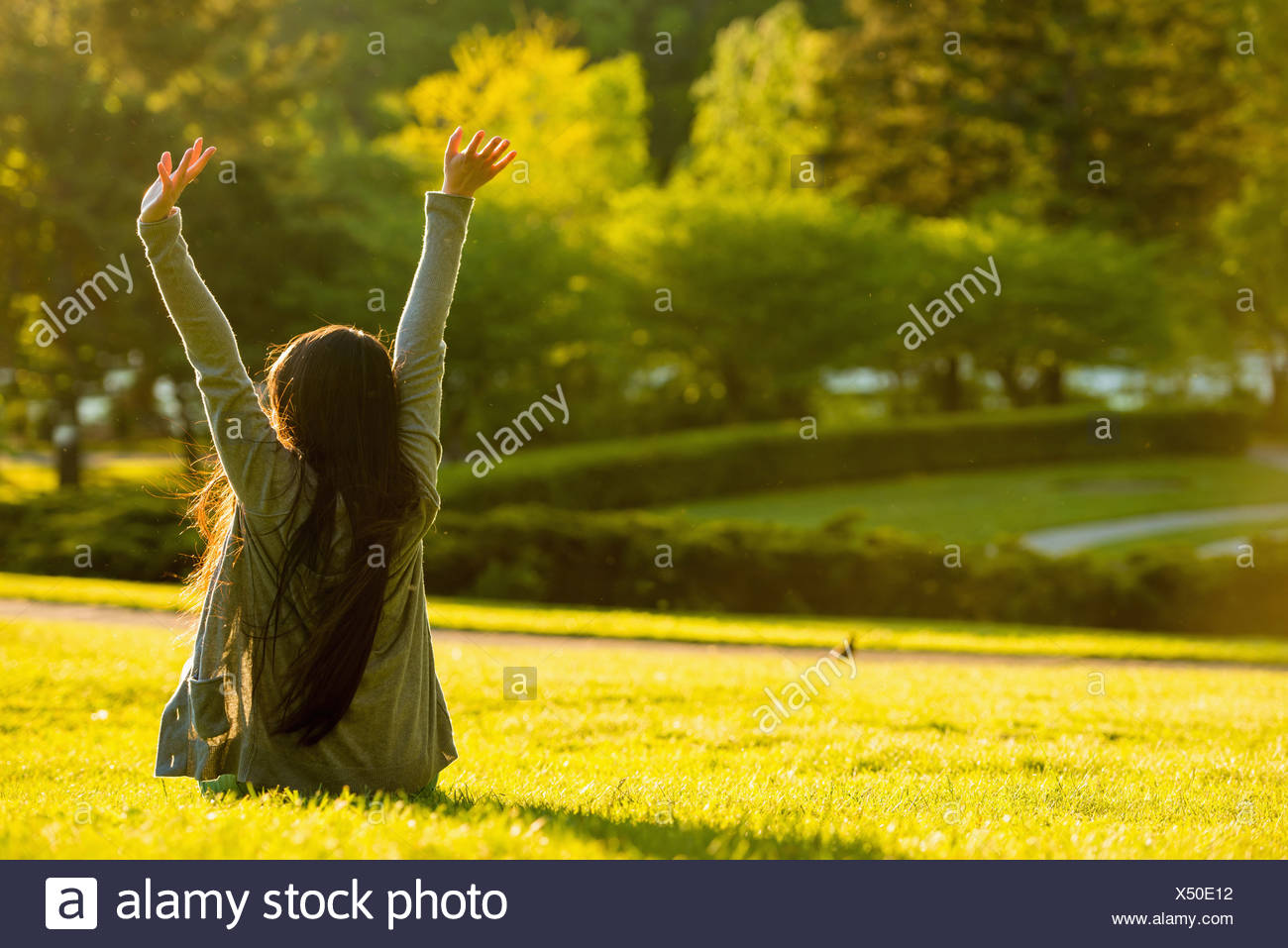 Young female sitting with arms raised in park - Stock Image