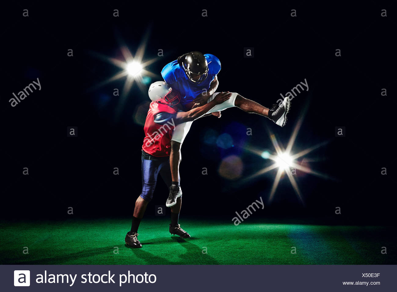 American football players jumping with ball Stock Photo