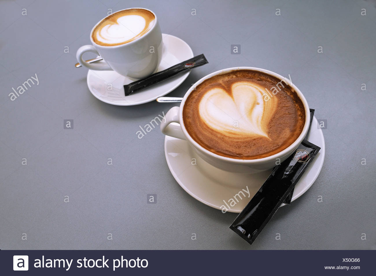 A large cup and a small cup of cappuccino with a heart shape in the milk foam Stock Photo