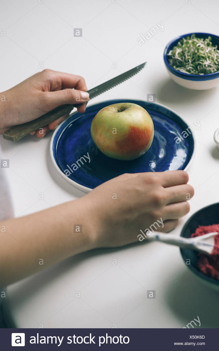Picture of apple on a blue handmade plate - Stock Image
