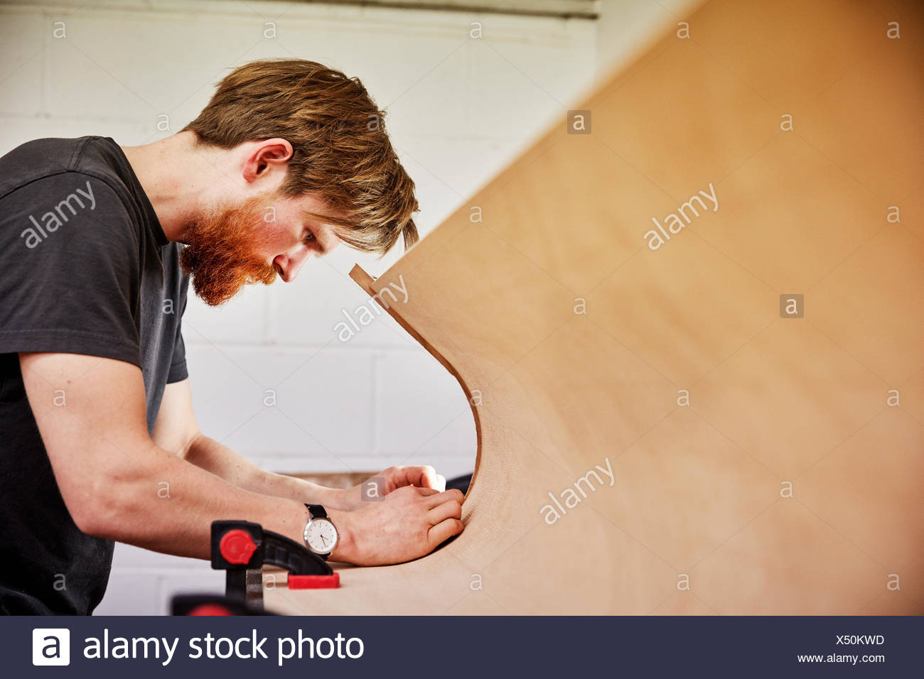 A  man using a tool on the curved cut out edge of a piece of wood - Stock Image