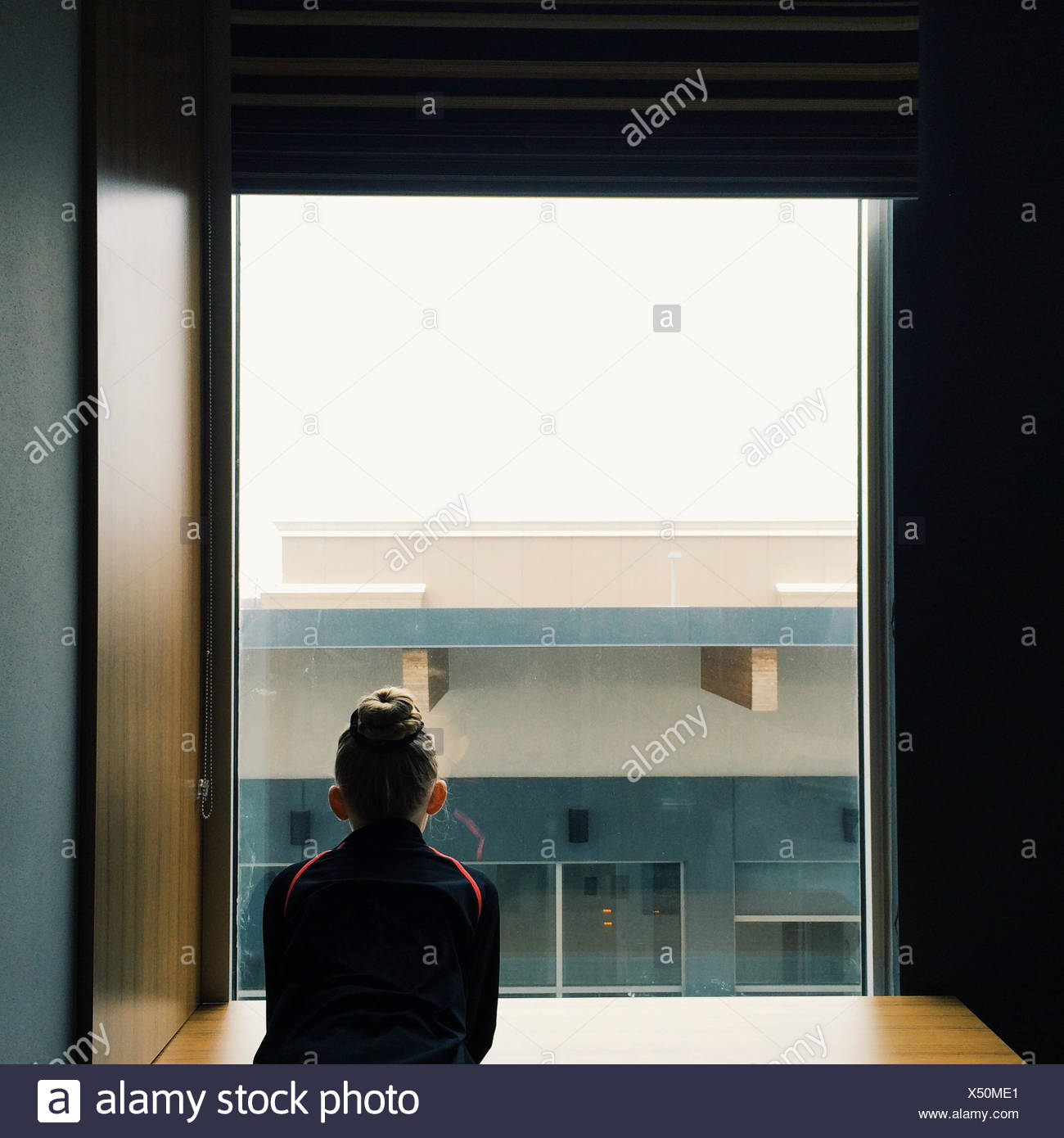 Girl (8-9) looking out of window Stock Photo