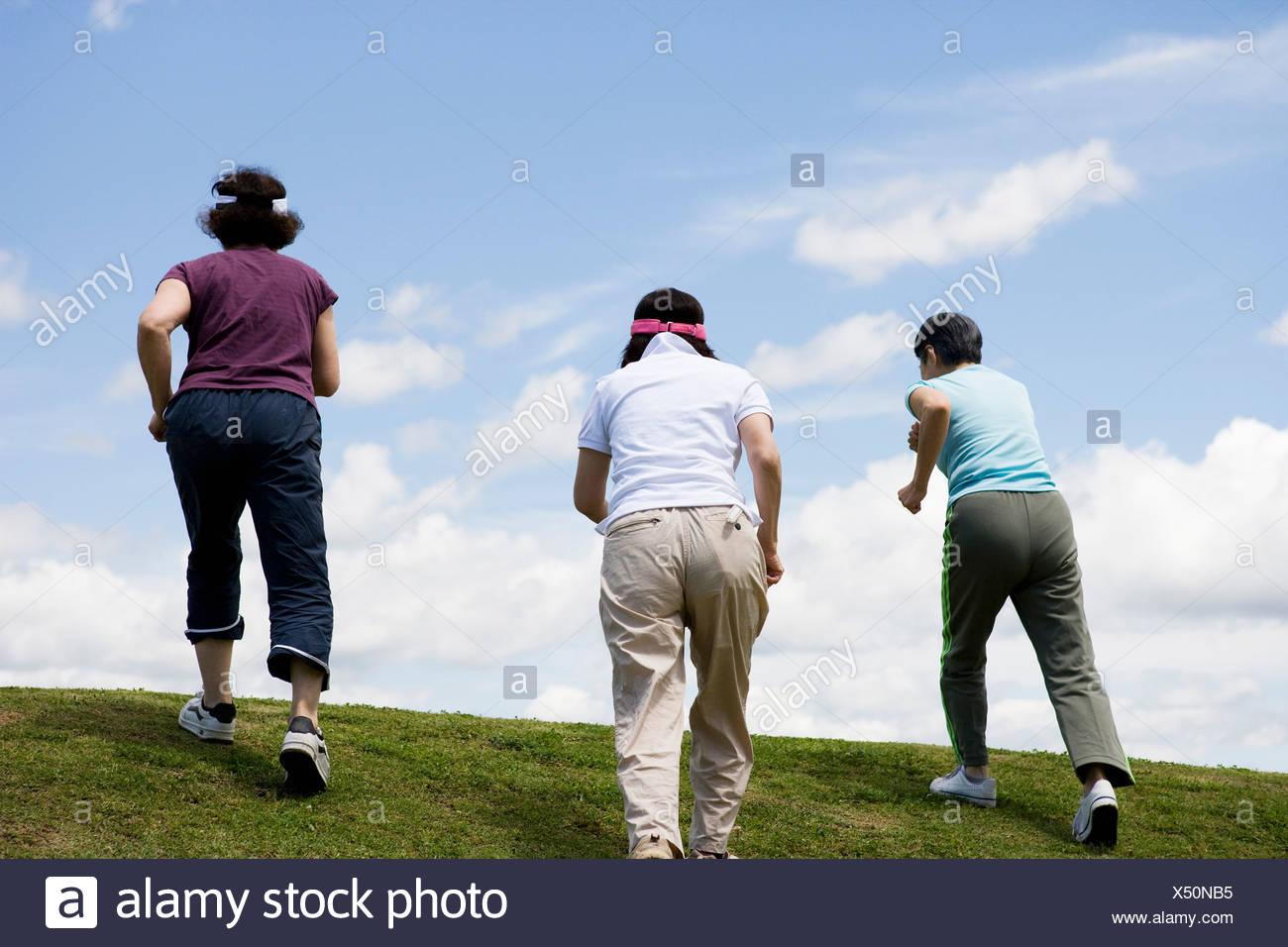 Three senior women walking up a hill - Stock Image