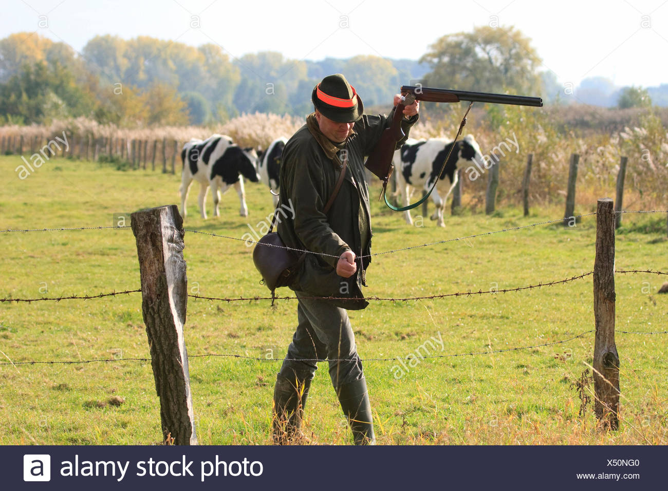 hunter climbing over the barbed wire fence at a pasture, Germany Stock Photo