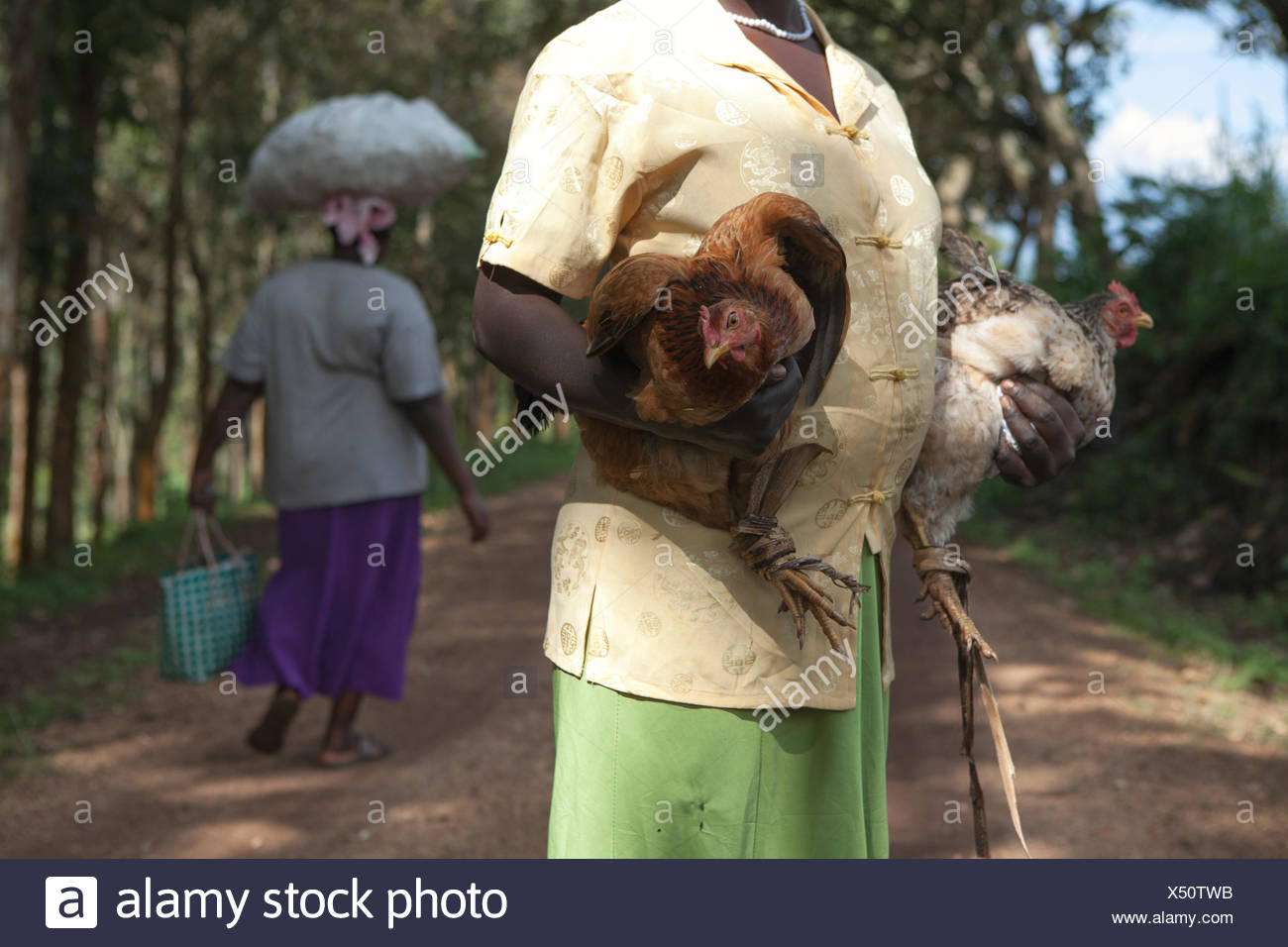 A woman stands in a path and carries two hens while another woman carries items on her head. - Stock Image
