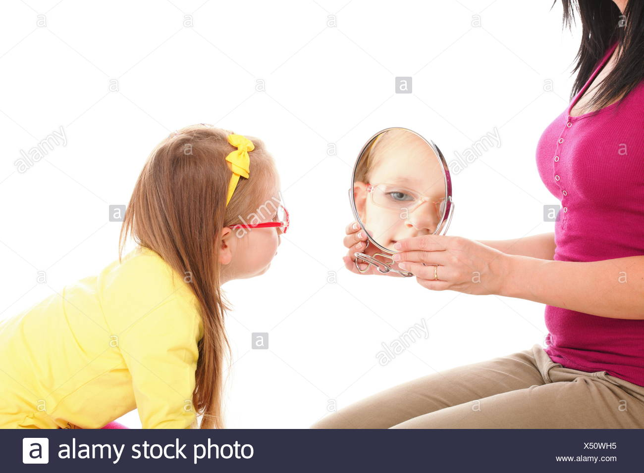 baby girl and mirror mother - Stock Image