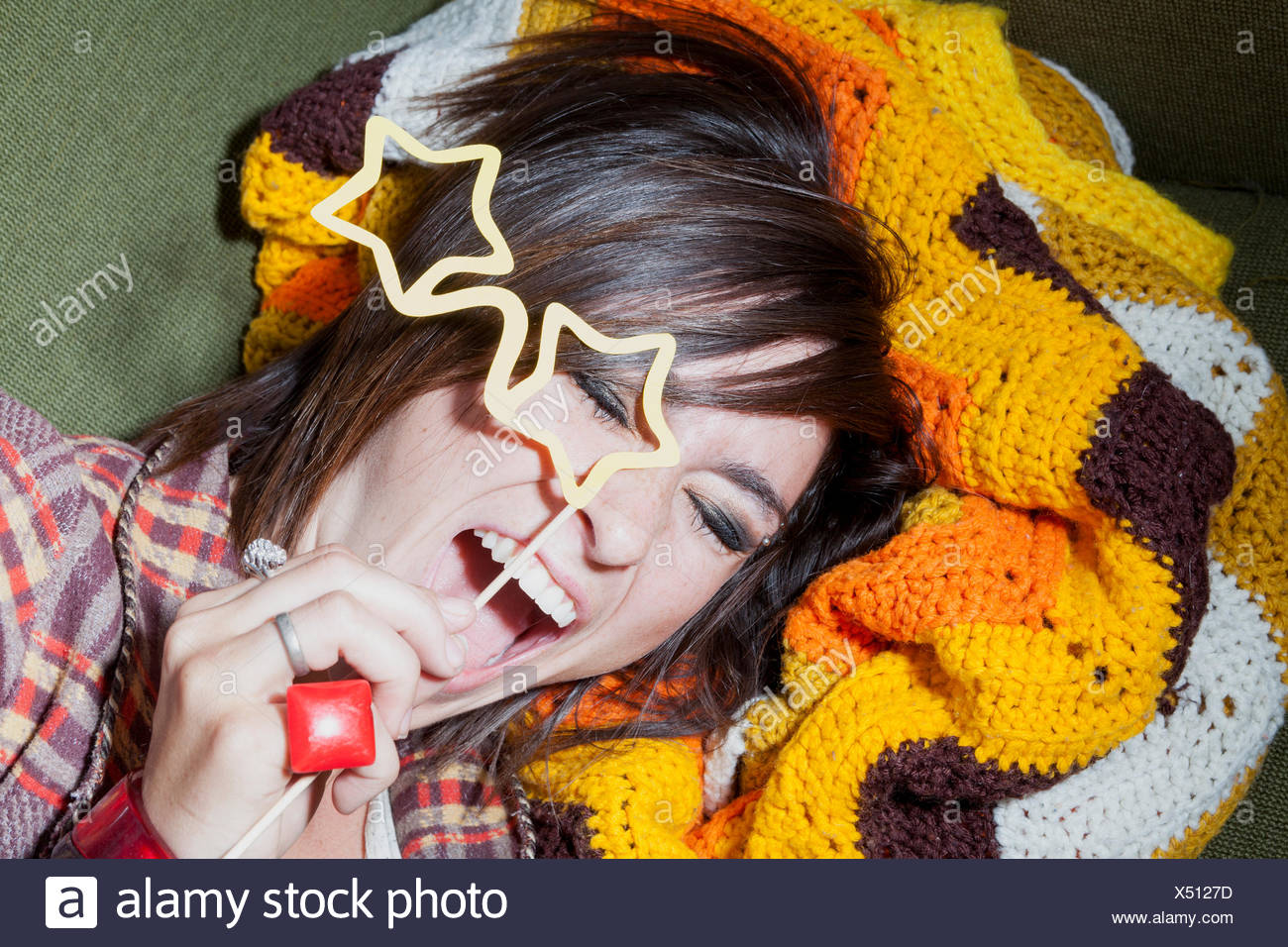 1970's style portrait of young woman holding star shaped spectacles - Stock Image