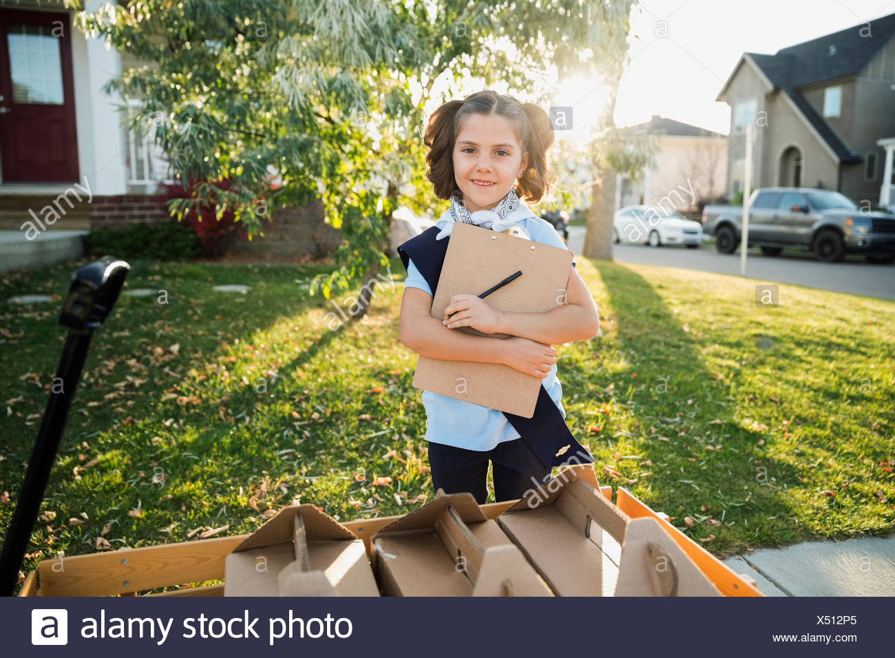 Portrait smiling girl scout with clipboard selling cookies - Stock Image