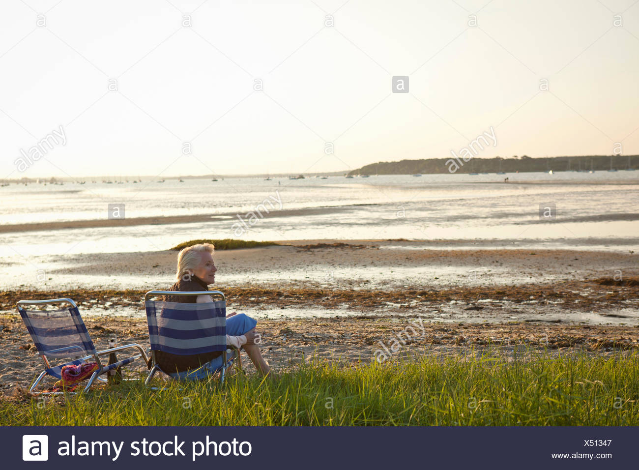 Senior woman relaxing by beach Stock Photo