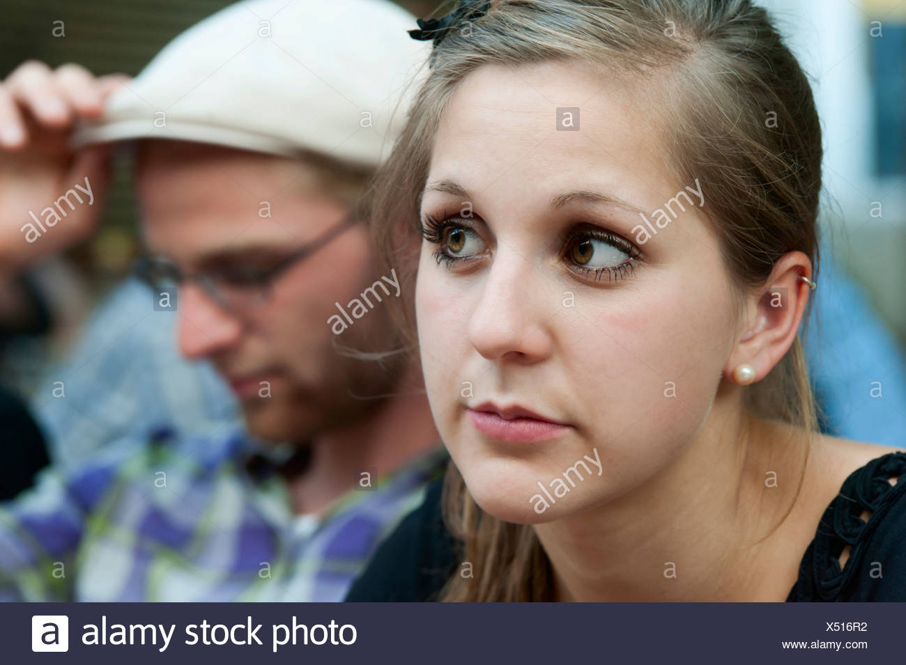 A young man and a young woman looking a bit bored, Germany, Europe - Stock Image
