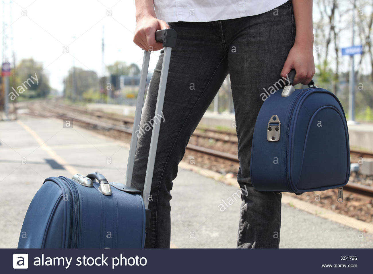 a man with luggage waiting for the train - Stock Image