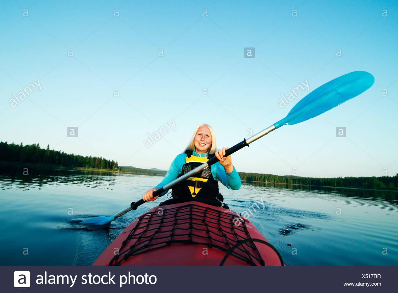 Smiling woman holding paddle - Stock Image