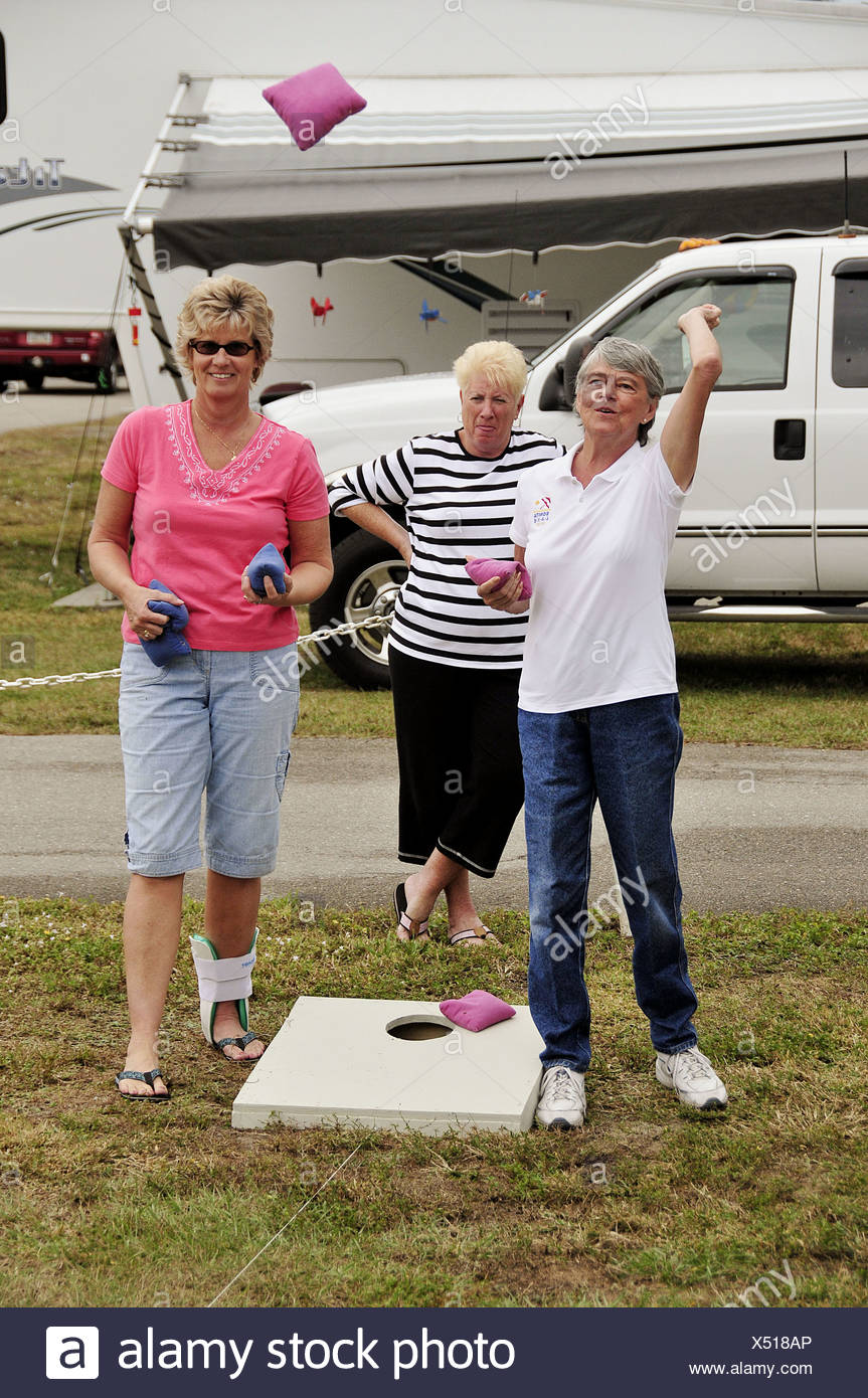 Female Senior retired citizens play game of bean bag toss in a recreational vechile camping park in Bonita Springs Florida - Stock Image