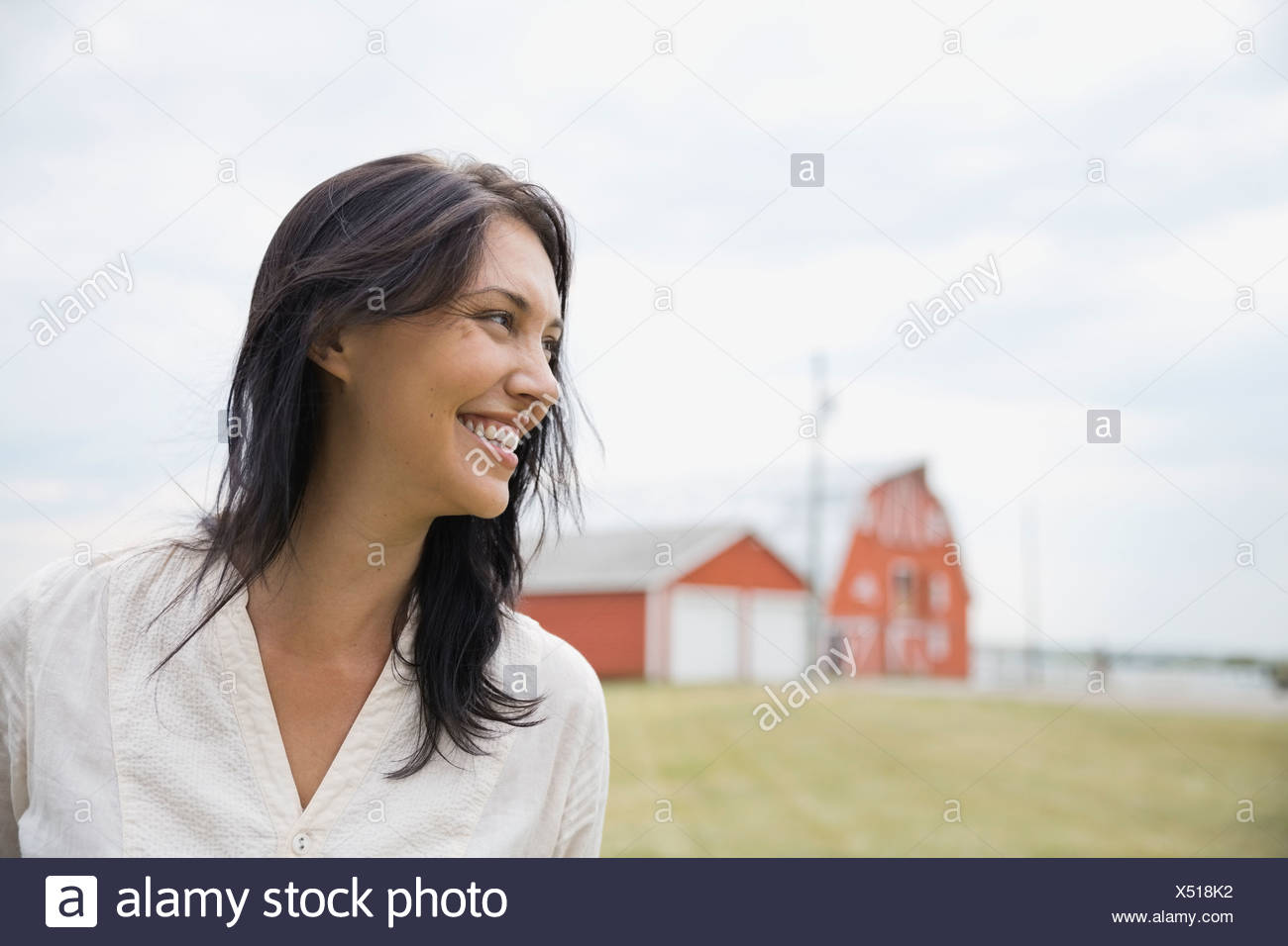 Portrait of smiling woman outdoors - Stock Image