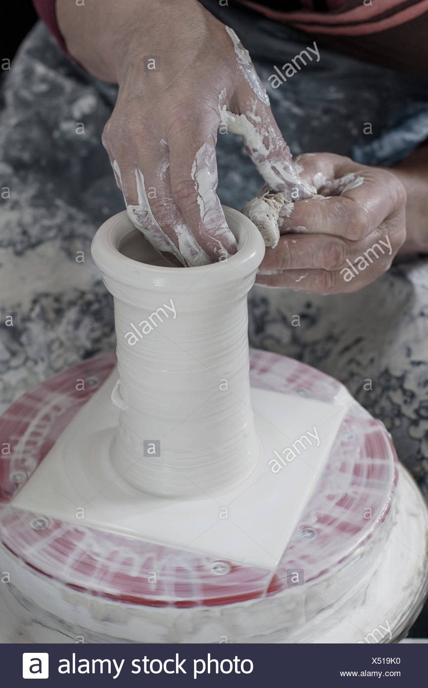 Close-up of female potter moulding clay using cleaning sponge in workshop, Bavaria, Germany - Stock Image