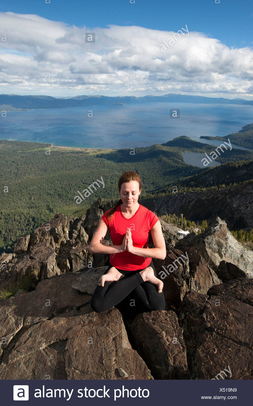 A woman performs yoga on top of Mount Tallac overlooking Lake Tahoe on a beautiful afternoon near South Lake Tahoe, CA. - Stock Image