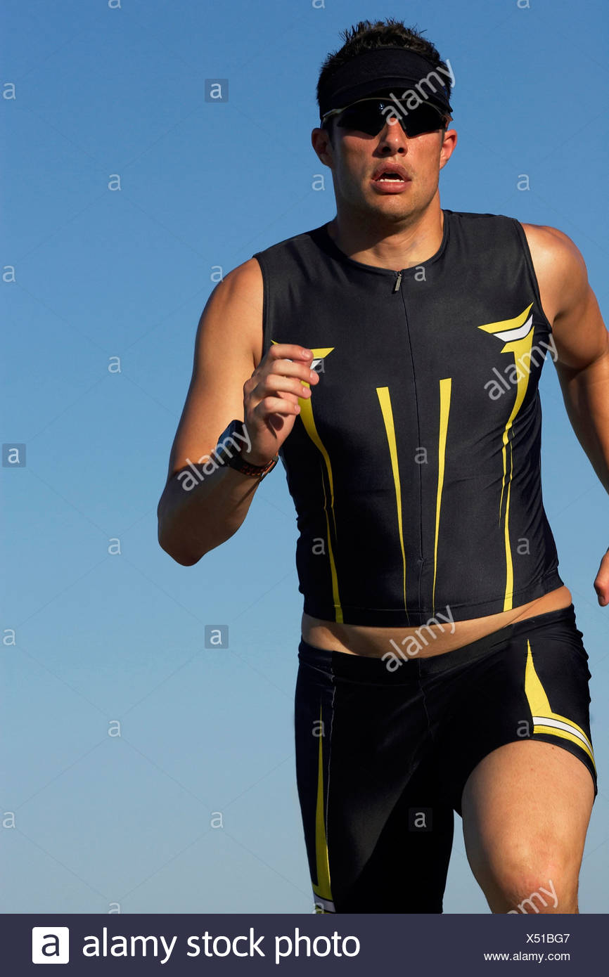 A male athelete running while training for a triathlon at a lake. - Stock Image