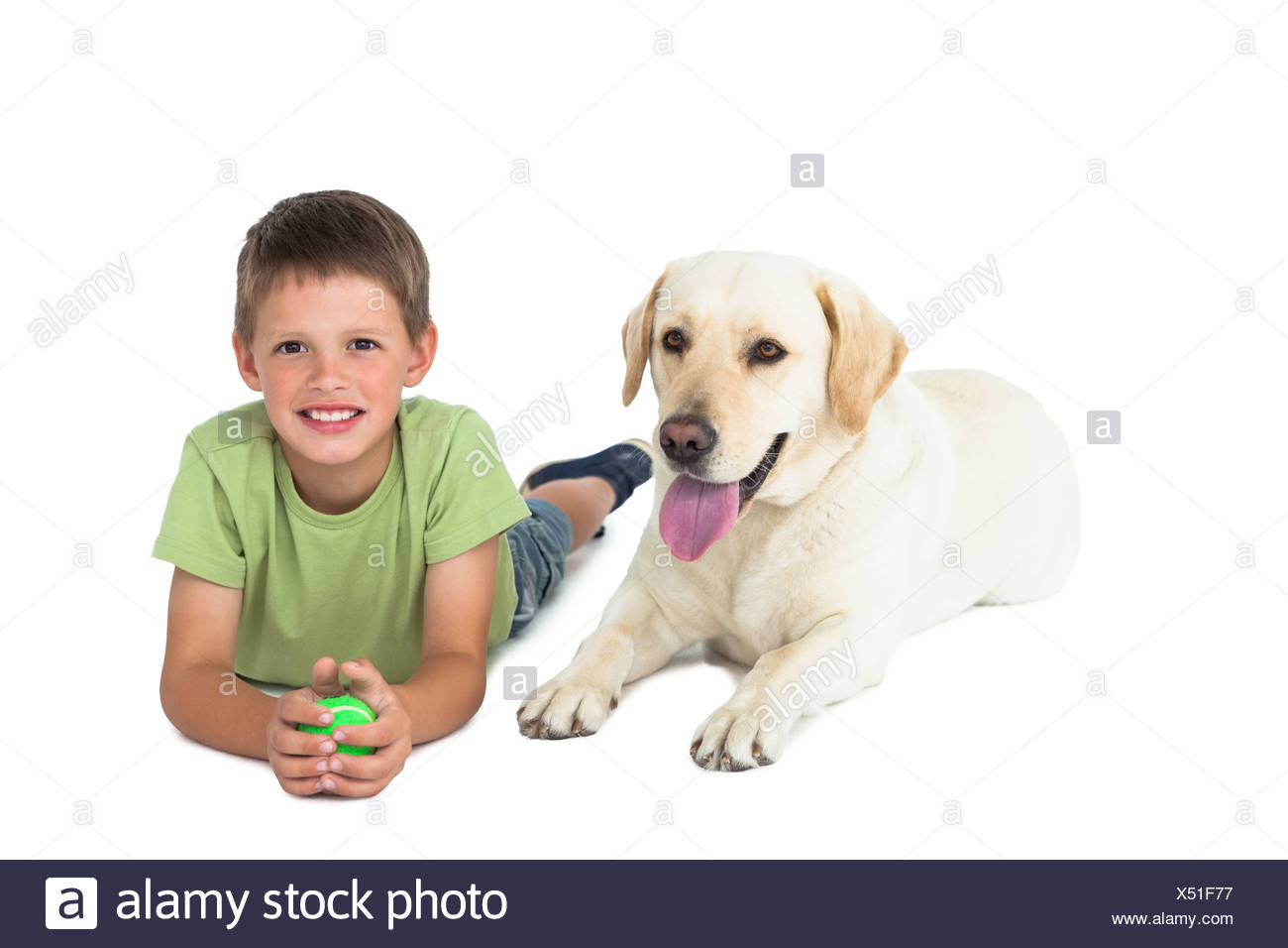 Cute little boy holding ball lying on floor with his labrador - Stock Image